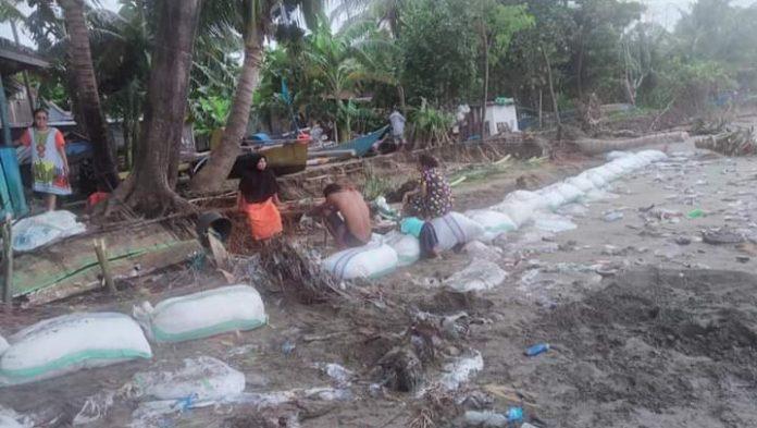 Warga Kampong Bakara Desa Pa'jukukang, Kecamatan Pa'jukukang yang mukim di pesisir pantai bergotong-royong membangun tanggul pasir penahan ombak