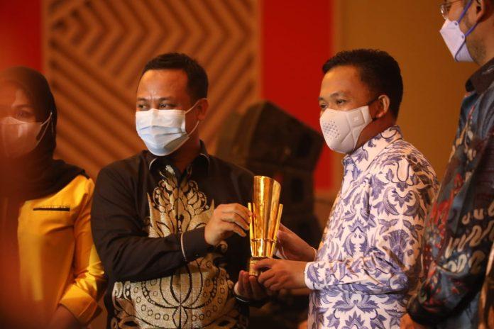 Bupati Bantaeng, H. Ilhamsyah Azikin, menerima tropi dari Plt. Gunernur Sulsel, Andi Sudirman Sulaiman, Kamis (8/4/2021). (Dok. Humas Pemkab Bantaeng)