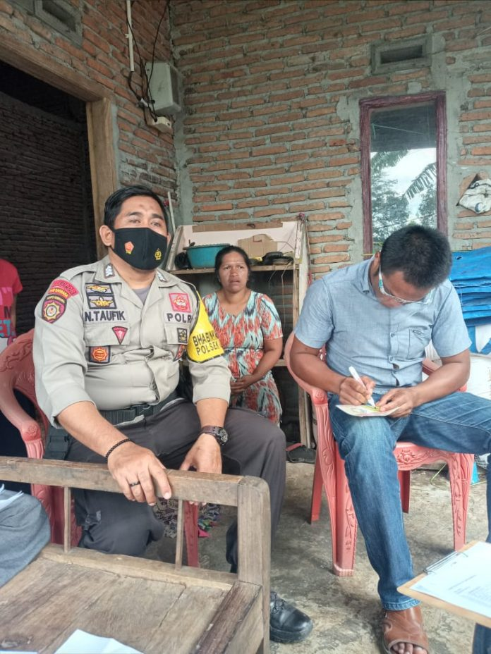 Bhabinkamtibmas Desa Kayu Loe, Bripka Nur Taufik, memantau pendataan yang dilakukan tim relawan SDGs. Foto: Syahran Azis