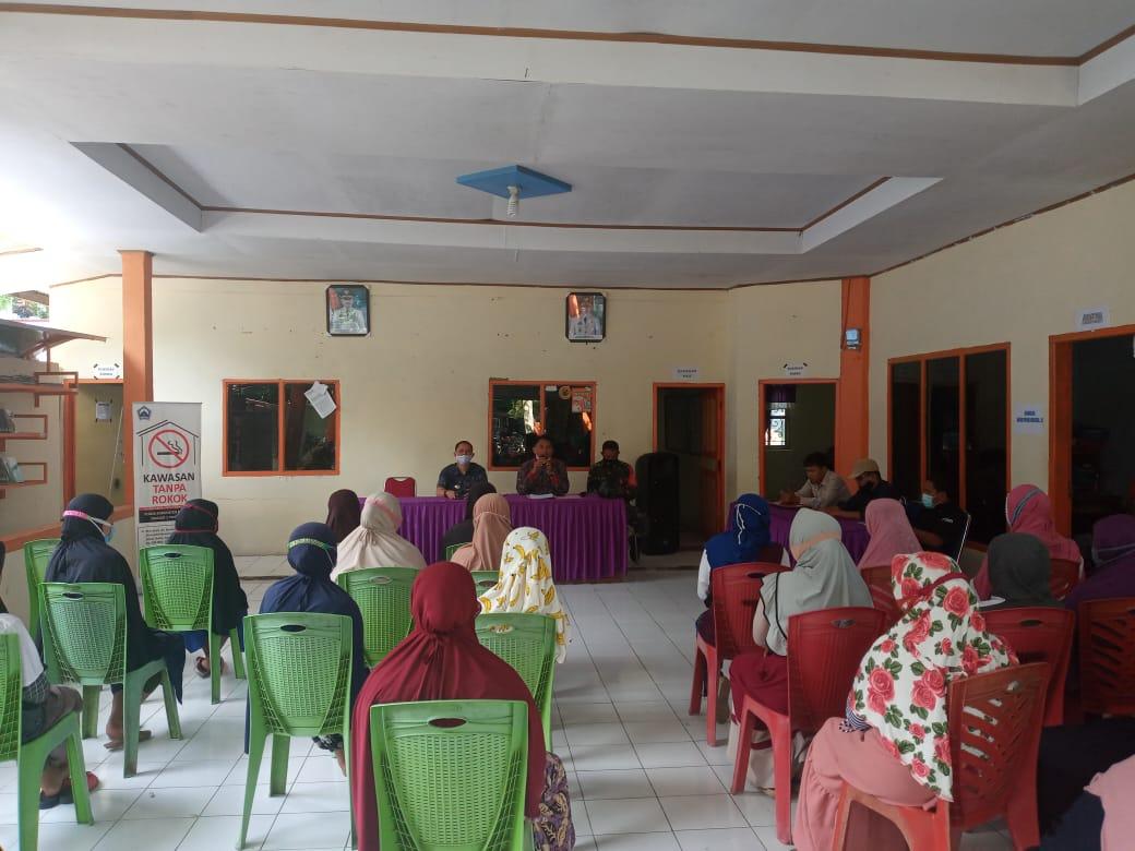 Keluarga Penerima Manfaat BLT DD Desa Tombolo sedang mendengarkan pengarahan dari Camat dan Kepala Desa